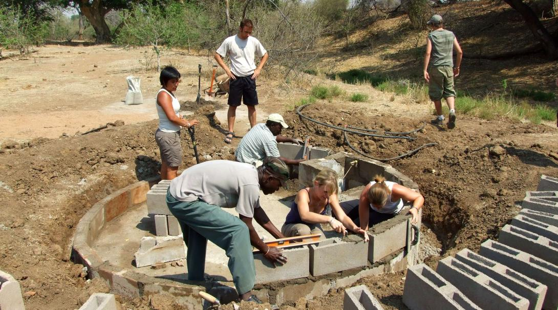 Projects Abroad conservation volunteers build a water hole in the reserve in Kenya for Lions, Giraffes and other animals.